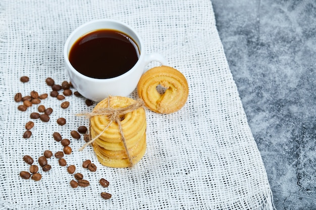 Stapel koekjes met koffiebonen en een kopje koffie op een wit tafelkleed.