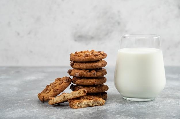 Stapel koekjes met pinda's en honing met glas melk op marmeren tafel.