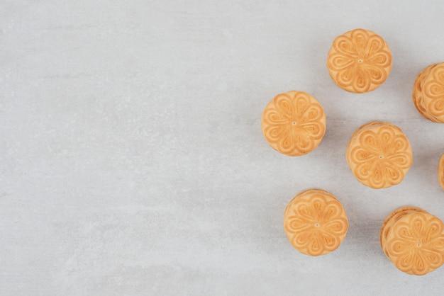 Stapel koekjes met room op witte achtergrond.