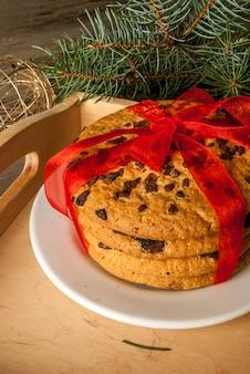 Stapel koekjes van kerstmis die met rood feestelijk lint worden gebonden. naast de kerstboomtak