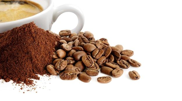Stapel koffie poeder koffiebonen en kopje espresso geïsoleerd op wit