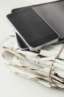 Stapel kranten met digitale tablet en smartphone