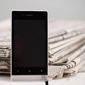 Stapel kranten met smartphone erop