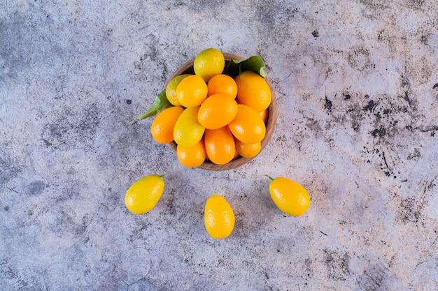 Stapel kumquats op rustiek.
