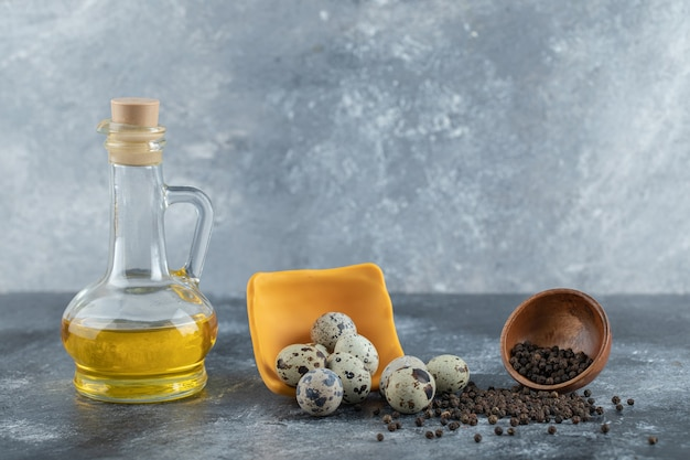 Stapel kwarteleitjes op grijze achtergrond met olie en kruiden