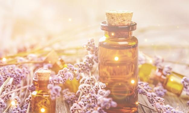 Stapel lavendelbloemen en een druppelflesje met lavendelessence