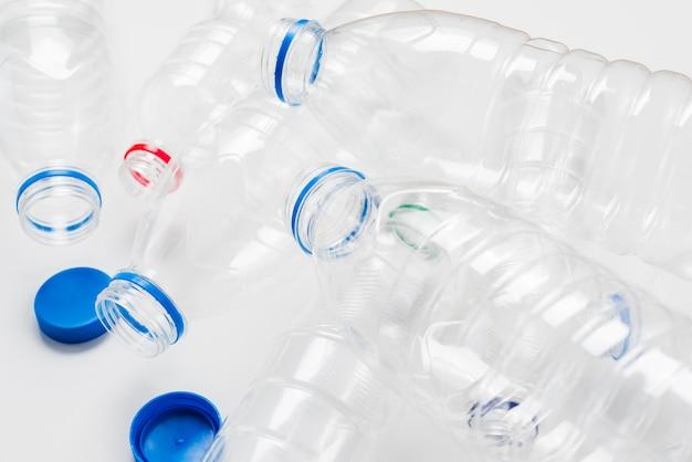 Stapel lege plastic flessen en doppen