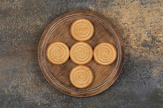 Stapel lekkere koekjes op houten plaat.