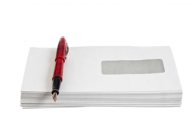 Stapel mail enveloppen en een pen op wit wordt geïsoleerd