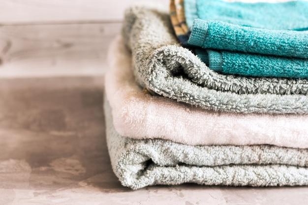 Stapel meerdere gekleurde handdoeken op een grijze achtergrond.