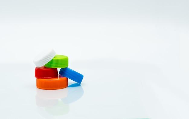 Stapel met verschillende afmetingen witte, groene, rode, blauwe en oranje ronde plastic schroefdoppen