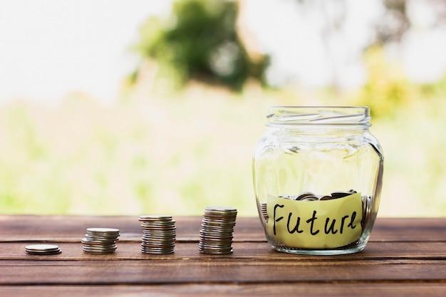 Stapel munten en pot met besparingen