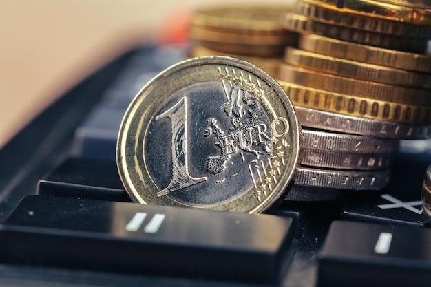Stapel munten en rekenmachine, concept voor zakelijke financiën