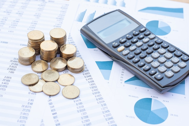 Stapel munten en rekenmachine op blauwe pastel grafiek papier. business, financiën, marketing, e-commerce concept.