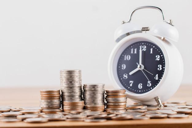 Stapel munten met klok voor het besparen van geld concept