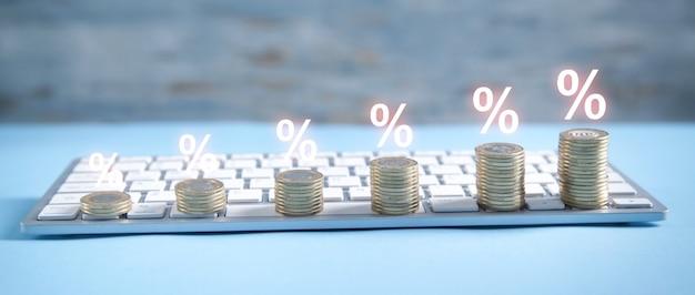 Stapel munten op het toetsenbord van de computer met een procent-symbolen.