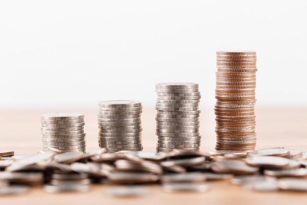 Stapel munten op houten bureau voor het besparen van geld concept
