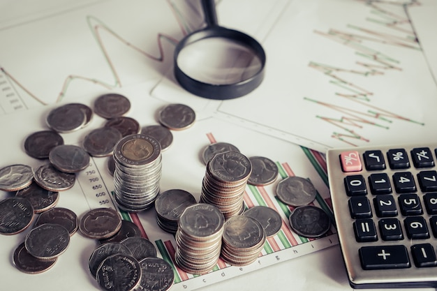 Stapel munten, rekenmachine op bureau