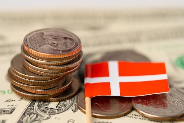 Stapel muntstukken met de vlag van denemarken op amerikaanse dollarsachtergrond.