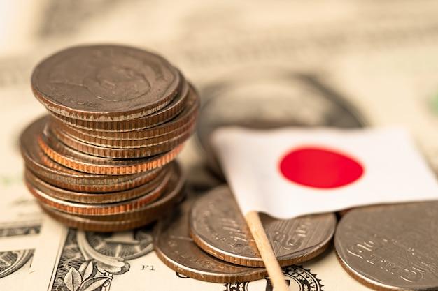 Stapel muntstukken met de vlag van japan op de dollarbankbiljetten van de vs amerika.