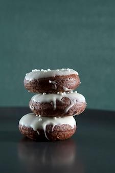 Stapel naar huis gebakken chocolade donuts met wit suikerglazuur en decoratieve ballen. verticale oriëntatie.