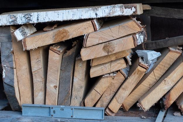 Stapel natuurlijke ongelijke ruwe houten planken van verschillende groottes, doorsnede. timmerhout voor de bouw, constructie en meubelen.