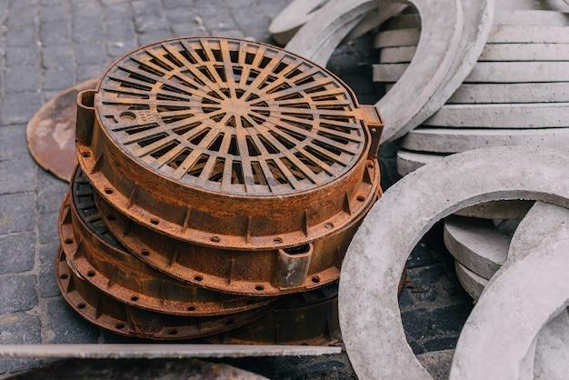 Stapel nieuwe industriële ronde concrete luiken voor het rioleringssysteem. riolering luik