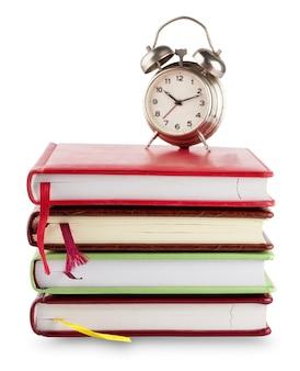 Stapel notebooks met bladwijzers en wekker