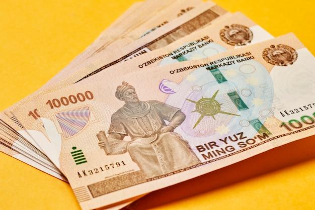 Stapel oezbeekse sommen oezbeekse geld op gele achtergrond