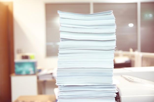 Stapel onafgemaakte documenten op gestapeld bureau.