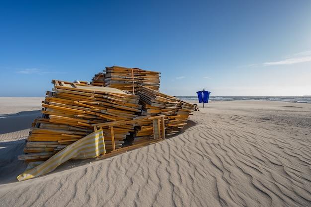 Stapel ongebruikte strandstoelen op een leeg strand