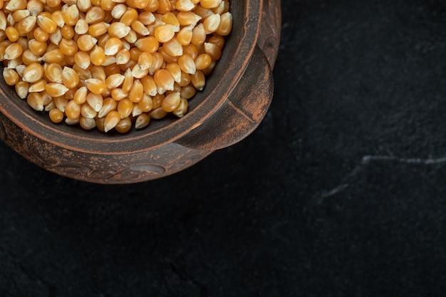 Stapel ongekookte maïskorrels in oude mok