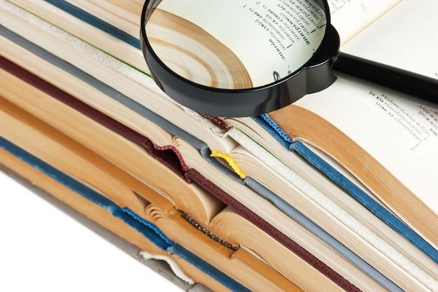 Stapel open boeken, en vergrootglas geïsoleerd