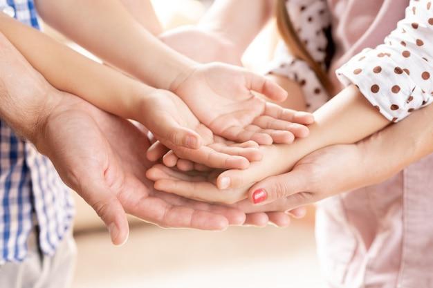 Stapel open palmen van jonge moeder, vader, hun zoontje en dochter symboliseert steun, zorg en liefde