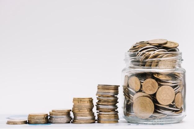 Stapel oplopende munten met pot gevuld met munten tegen witte achtergrond