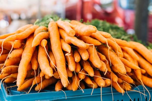 Stapel oranje geoogste wortelen in de boerderijmarkt