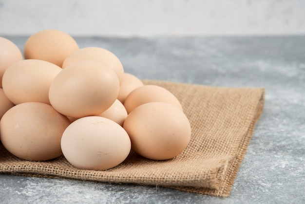Stapel organische ongekookte eieren met tafelkleed op marmeren oppervlak.