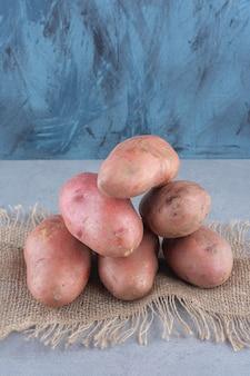 Stapel organische rode aardappel op zak.