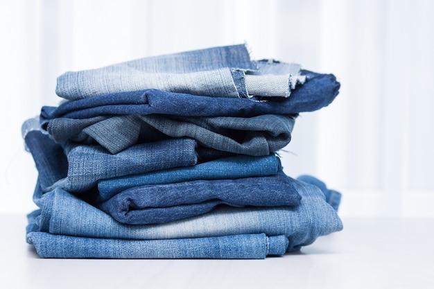 Stapel oude blauwe spijkerbroek voor recycling op witte achtergrond.
