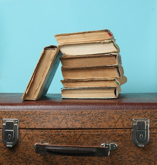 Stapel oude boeken op retro koffer op blauw