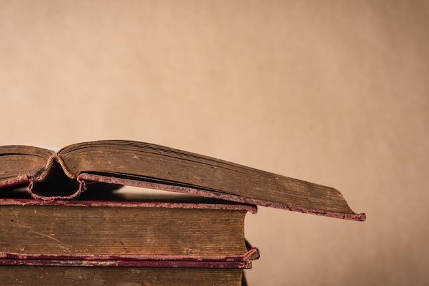 Stapel oude boeken op uitstekende bruine muurachtergrond