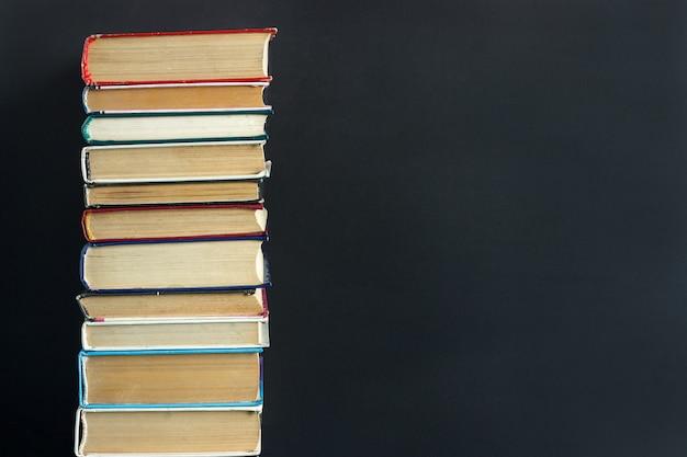 Stapel oude boeken op zwart schoolbord als achtergrond