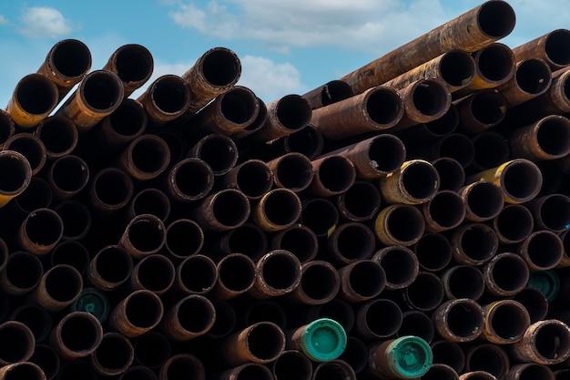 Stapel oude roestige ronde metalen industriële pijp. stalen pijpstapel in magazijn van fabriek. industrieel materiaal. metaal corrosie. stapel roestige buis. oude ijzeren pijp in magazijn. industrie van metalen buizen.