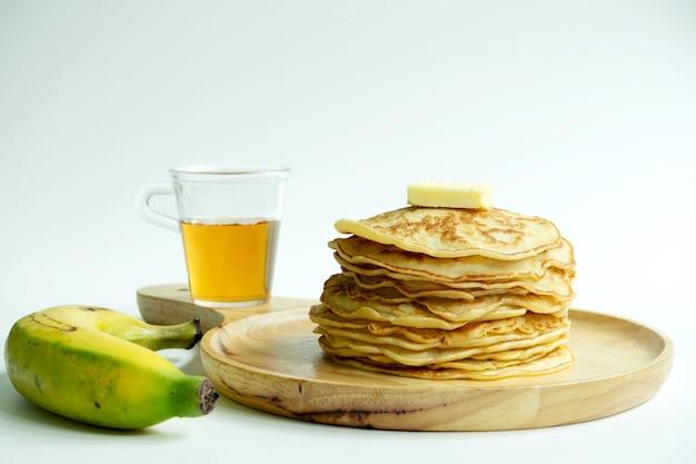 Stapel pannekoeken met honingsstroop, boter en banaan op witte achtergrond