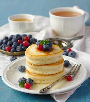Stapel pannekoeken met verse bessen en honing