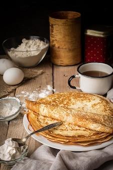 Stapel pannenkoeken en ingrediënten voor het koken op een tafel