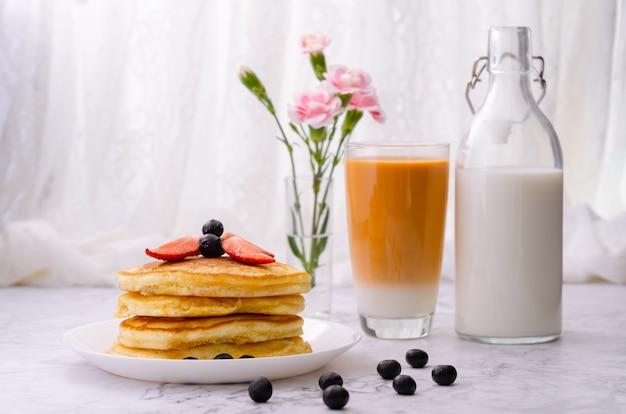 Stapel pannenkoeken met verse aardbeien en bosbessen op een witte plaat, een fles melk, een glas melkthee en een vaas met roze bloemen op marmeren tafel