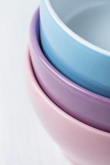 Stapel pastelkleur multicolored kommen op witte houten lijst. vakantie bakken concept koken