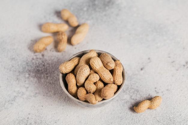 Stapel pinda's in een kom op een witte achtergrond. verse noten in hun schelpen.