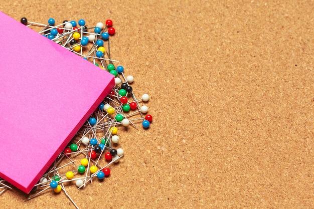 Stapel plaknotities omringd met een heleboel kleurrijke push pins